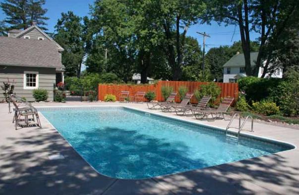 Backyard patio with inground pool and lounge chairs