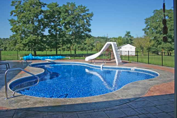 inground pool with a water slide and diving board